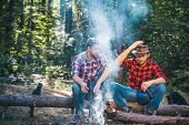 Happy Friends On A Camping Trip Relaxing By Campfire. Friends Relaxing Near Campfire After Day Hikin poster