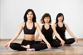 Slim Brunettes Women In Yoga Pose, Sitting On Floor On Mat In Row, Looking On Camera, Relaxing Makin poster
