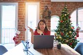Beautiful woman sitting at the table working with laptop at home around christmas tree Pointing asid poster