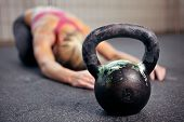 stock photo of kettles  - Young woman stretching her back after a heavy kettlebell workout in a gym - JPG