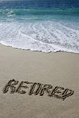 The word RETIRED written in the sand at the ocean.  Retirement gives you more time for fun vacation  poster