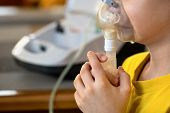 Child Makes Inhalation At Home With Nebulizer On Out Of Focus Background. Example Of Combating Respi poster
