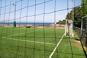 Look Through Net To Empty Football Field In Soccer Stadium. Soccer Field With Green Grass In Footbal poster