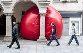 Three men look at Kurt Perschke's giant Red Ball that was squeezed into the entrance of the Guildha