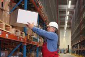 Worker In Uniform Putting Box On Shelves In Warehouse