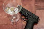 image of top-gun  - closeup of a martini on a bar top with an out of focus gun - JPG