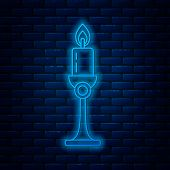 Glowing Neon Line Burning Candle In Candlestick Icon Isolated On Brick Wall Background. Old Fashione poster