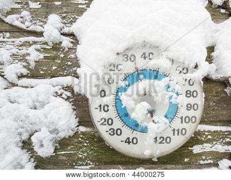 Thermometer in the snow on side of barn