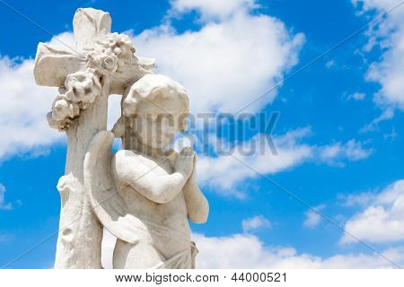 Beautiful infant angel leaning on a christian cross with a blue sky background (with space for text)