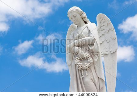 Beautiful white angel with a blue sky background (with space for text)