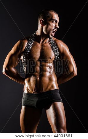 Muscular man with chain on black background