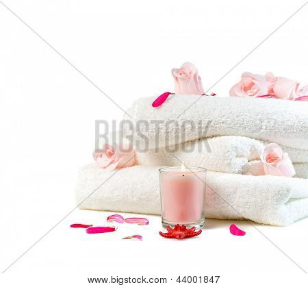 white towels with pink flowers and candle isolated on white background