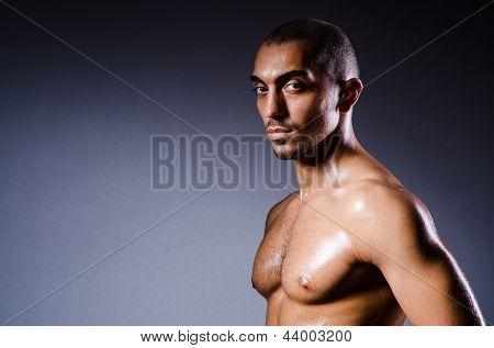 Hombre musculoso en estudio oscuro