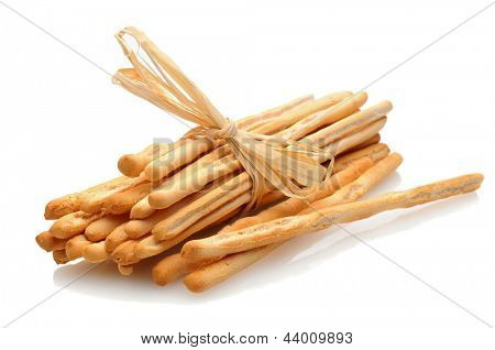 Breadsticks laying on a white surface with reflection. Bread sticks are tied with rafia. Horizontal format