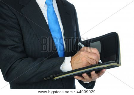 Closeup of a businessman taking notes in a small notebook. Hands and torso only, man is unrecognizable. Horizontal format over a white background.