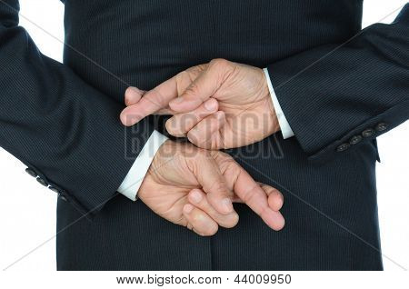 Closeup of a business man with his hands behind his back and fingers crossed. Torso and hands only, man is unrecognizable.