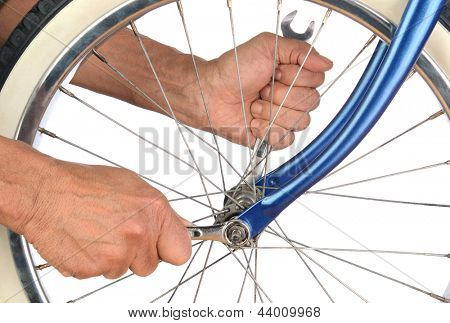 Closeup of a mans hands tightening the bolts on a bicycle wheel.