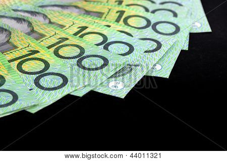 Australian one hundred dollar bills fanned over black background.