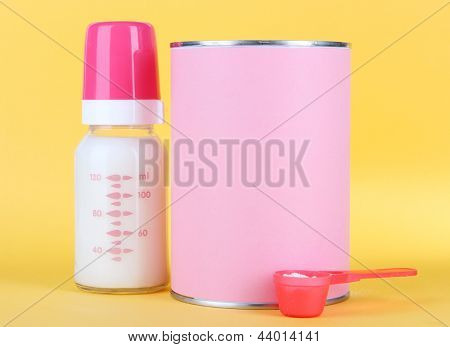 Powdered milk with baby bottle of milk on yellow background
