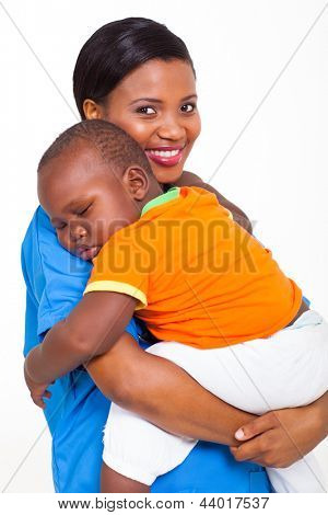 portrait of beautiful young african nurse carrying sleeping baby boy