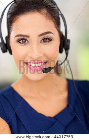 Closeup portrait of a happy young call centre employee smiling with a headset