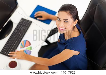 overhead view of female corporate worker working by her desk