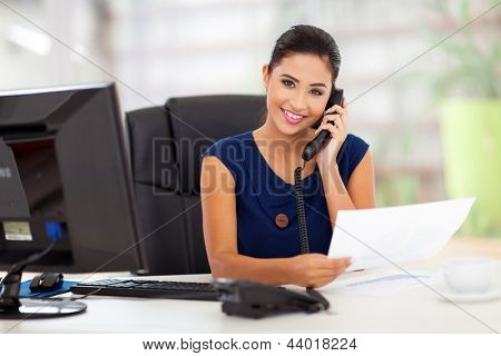 portrait of young secretary answering telephone