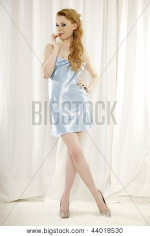 portrait of a beautiful adult sensuality blonde woman in blue lingerie on light background
