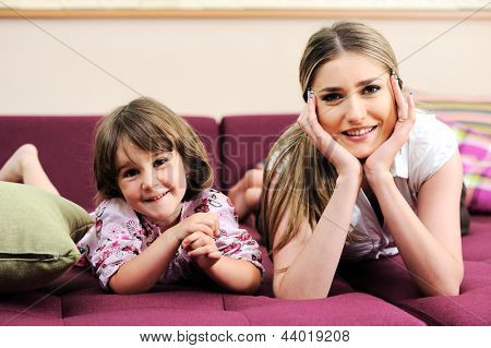 Young mom and her little son together on couch in living room