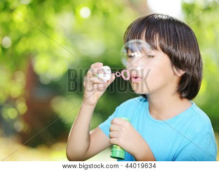 Portrait of cute little kid making soap bubbles. Free copy space