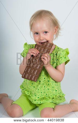 Young Girl Eating Bar Of Chocolate