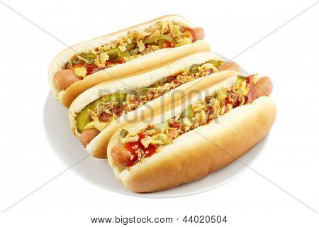 Three hot dogs on a plate isolated on white