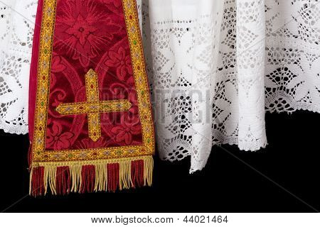 Closeup of a red vestment set of maniple and white lace priest surplice