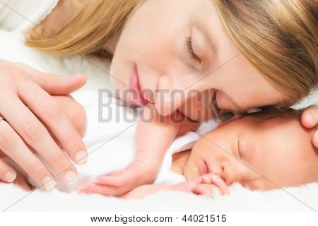 Tender mother lying cheek to cheek with her newborn baby of 11 days old