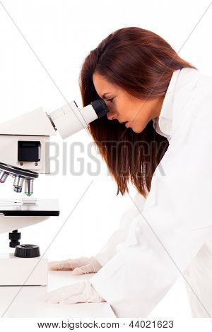 Young female researcher looking into a microscope, isolated on white background