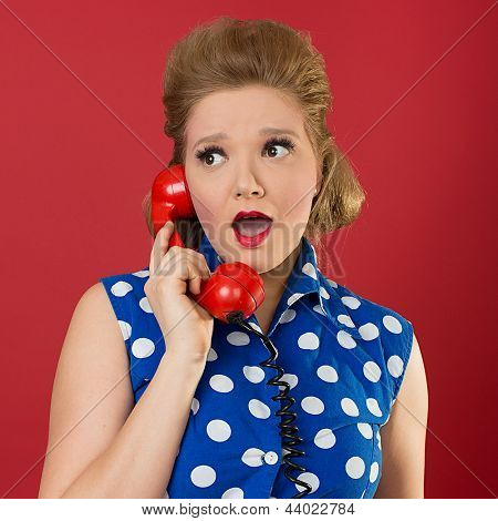 Photo of a young woman listening on the phone with a shocked expression on her face.