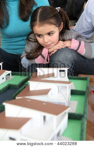 Young family sat with scale model of new home