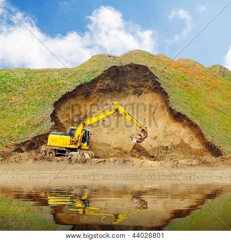 An excavator in old mine. Damaged landscape before recultivation.