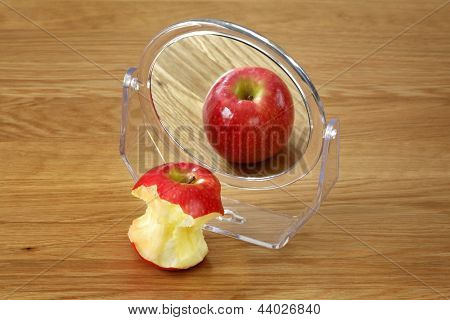 Metaphor for anorexia or bulimia eating disorder, apple in front of a mirror