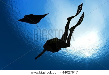 Girl with a diving under the water on a blue background.