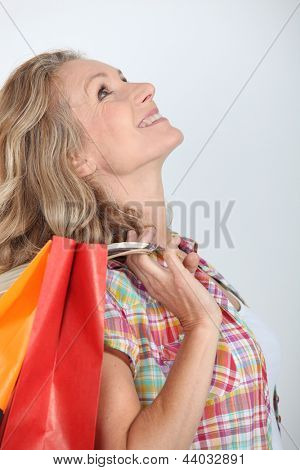 Studio shot of woman looking up holding store bags over her shoulder