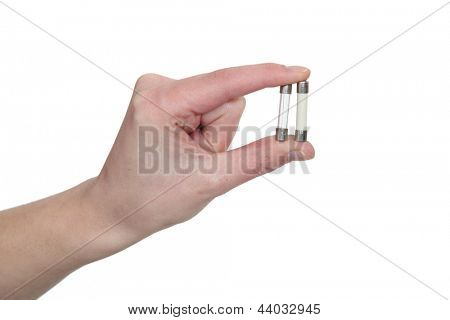 A hand holding two fuse wires.