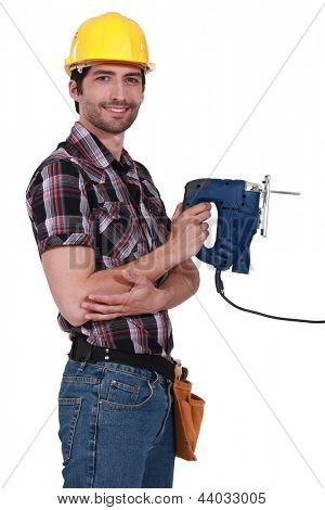 Handsome carpenter holding electric saw