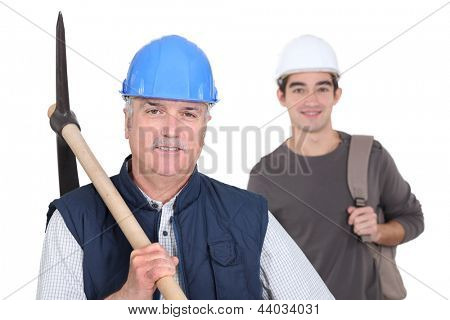 mature manual worker and young apprentice in background