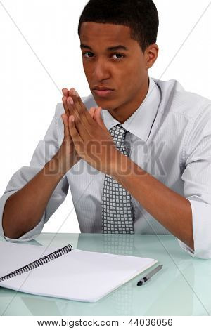 Uninspired young man sitting in front of an empty notebook