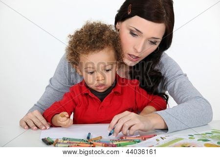 Little boy and mother drawing with crayons