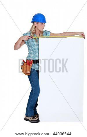 Construction worker measuring a blank board