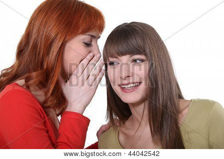 Young woman whispering a secret into her friend's ear