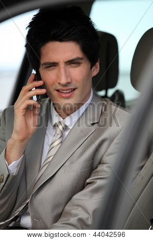 Businessman making call from parked car