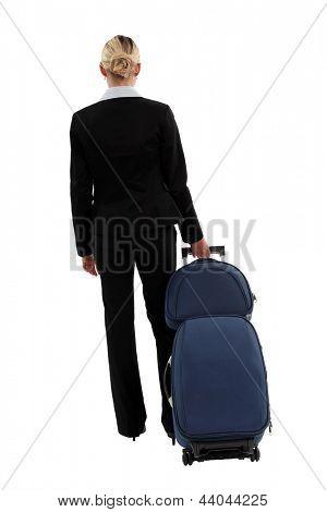 studio shot of businesswoman pulling luggage